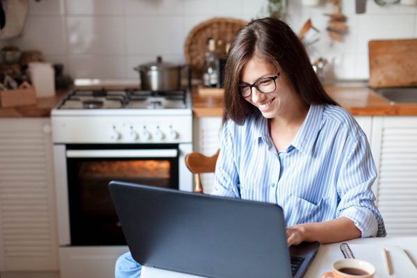 Young woman working from home office. Freelancer using laptop and the Internet for shopping online.